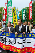 Leader of the Japanese Communist party, Shii Kazuo leads thousands of people in the 88th May Day rally in Central Tokyo to mark International Workers` Day. Tokyo, Japan. Monday, May 1st 2017 The rally started at 9am in Yoyogi Park near Shibuya and the march began at 12:30 despite heavy rain and thunderstorms. The rally called for an end to overwork in Japan along with other labour issues and  protested traditional left wing subjects such as nuclear power and weapons, and Prime Minister Shinzo Abe's plans to reinterpret  Article 9 of the Japanese constitution, thus making the Japanese military Self Defence Force able to fight wars alongside its allies.