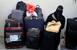 October 19, 2016 - Rafah, Gaza Strip - Palestinian woman in burka waits with her luggage for travel permits to cross into Egypt through the Rafah border crossing after it was opened by Egyptian authorities for humanitarian cases. (Credit Image: © Abed Rahim Khatib/APA Images via ZUMA Wire)
