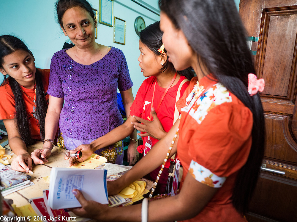 03 NOVEMBER 2015 - YANGON, MYANMAR:  NLD outreach workers (right) talk to residents in a Yangon tenement building during a voter outreach program. Political parties are wrapping up their campaigns in Myanmar (Burma). National elections are scheduled for Sunday Nov. 8. The two principal parties are the National League for Democracy (NLD), the party of democracy icon and Nobel Peace Prize winner Aung San Suu Kyi, and the ruling Union Solidarity and Development Party (USDP), led by incumbent President Thein Sein. There are more than 30 parties campaigning for national and local offices.       PHOTO BY JACK KURTZ