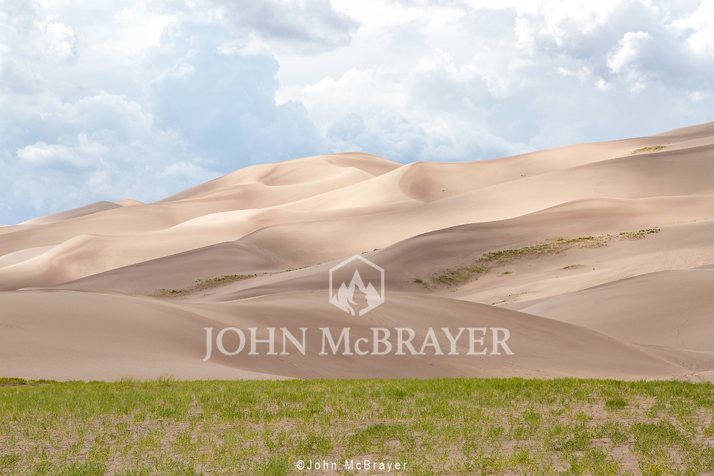 The colors of the Great Sand Dunes give the image a painting-like feeling.  This was a great place to explore, you get the dunes and sand without the heat. © John McBrayer