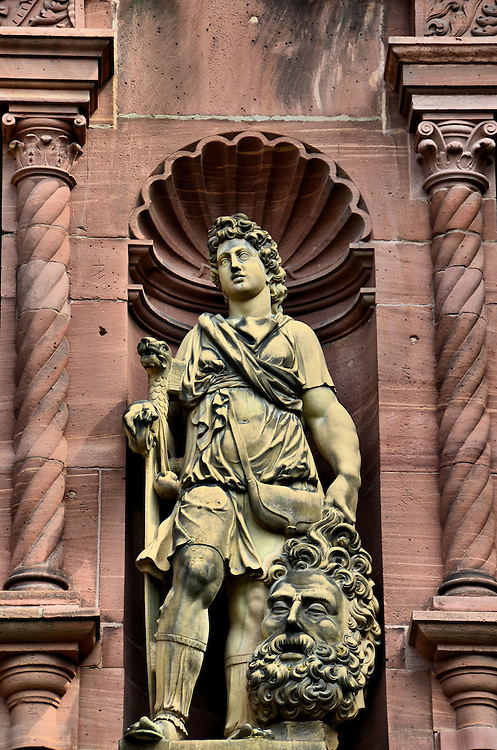 Heidelberg Castle David and Goliath Sculpture in Heidelberg, Germany <br /> This sandstone statue of David holding the head of the slain giant Goliath is the work of Alexander Colin, a Flemish master sculptor in the 16th century. It is in a niche of the Ottheinrichsbau at the Heidelberg Castle along with other figures from the Bible, mythical deities and the Virtues.