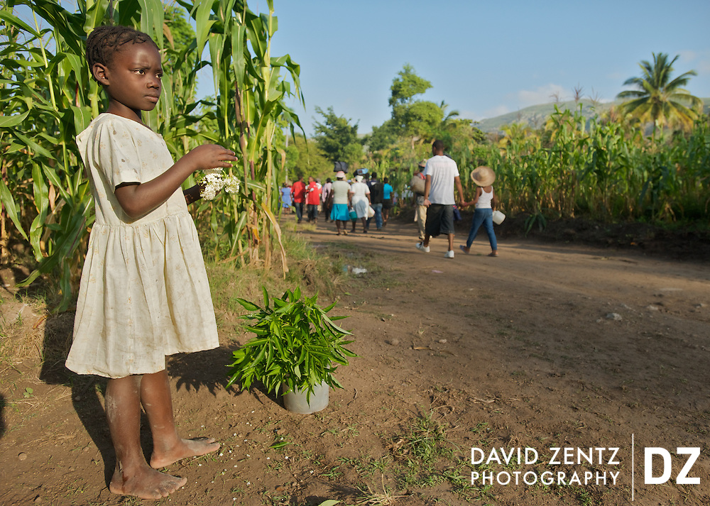 A young girl stands along a long dirt road leading from the village of Saut D'eau to the waterfall it is known for during the annual voodoo pilgrimage held there each July.