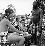 Two men participating in a drum workshop while a crowd follows, at Glastonbury, 1989.