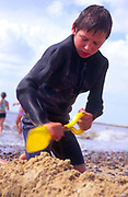 AJDM8F Young boy in black wet suit digging sand with yellow spade on beach