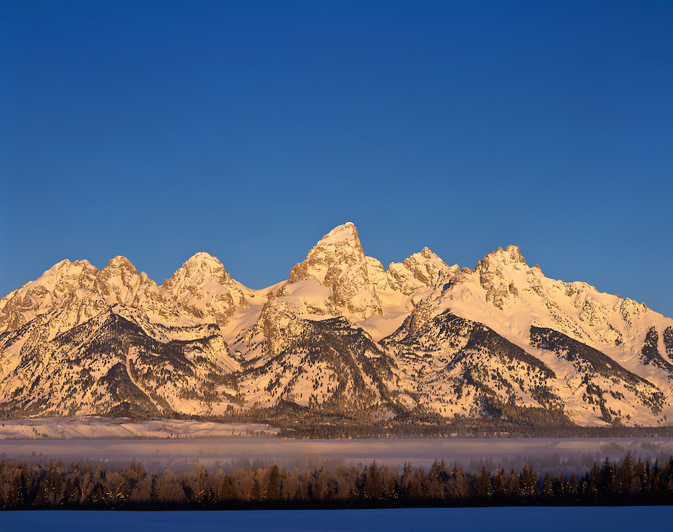 Winter sunrise on the Teton Range is a mountain range of the Rocky Mountains in North America. A north-south range, it is on the Wyoming side of the state's border with Idaho, just south of Yellowstone National Park. Most of the range is in Grand Teton National Park.<br /> <br /> Early French Voyageurs used the name &quot;les Trois T&eacute;tons&quot; (the three breasts).[1] It is likely that the Shoshone people once called the whole range Teewinot, meaning &quot;many pinnacles&quot;.[2]<br /> <br /> The principal summits of the central massif, sometimes referred to as the Cathedral Group, are Grand Teton (13,770 feet (4,200 m)), Mount Owen (12,928 feet (3,940 m)), Teewinot (12,325 feet (3,757 m)), Middle Teton (12,804 feet (3,903 m)) and South Teton (12,514 feet (3,814 m)). Other peaks in the range include Mount Moran (12,605 feet (3,842 m)), Mount Wister (11,490 feet (3,500 m)), Buck Mountain (11,938 feet (3,639 m)) and Static Peak (11,303 feet (3,445 m)).