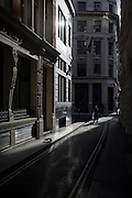 Sunlit street corner and pigeon in the City of London