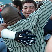Tim Dawson II, Yale, is hugged after Yale's overtime win during the Yale V Army, Football match at Yale Bowl, New Haven, Connecticut, USA. 27th September 2014. Photo Tim Clayton