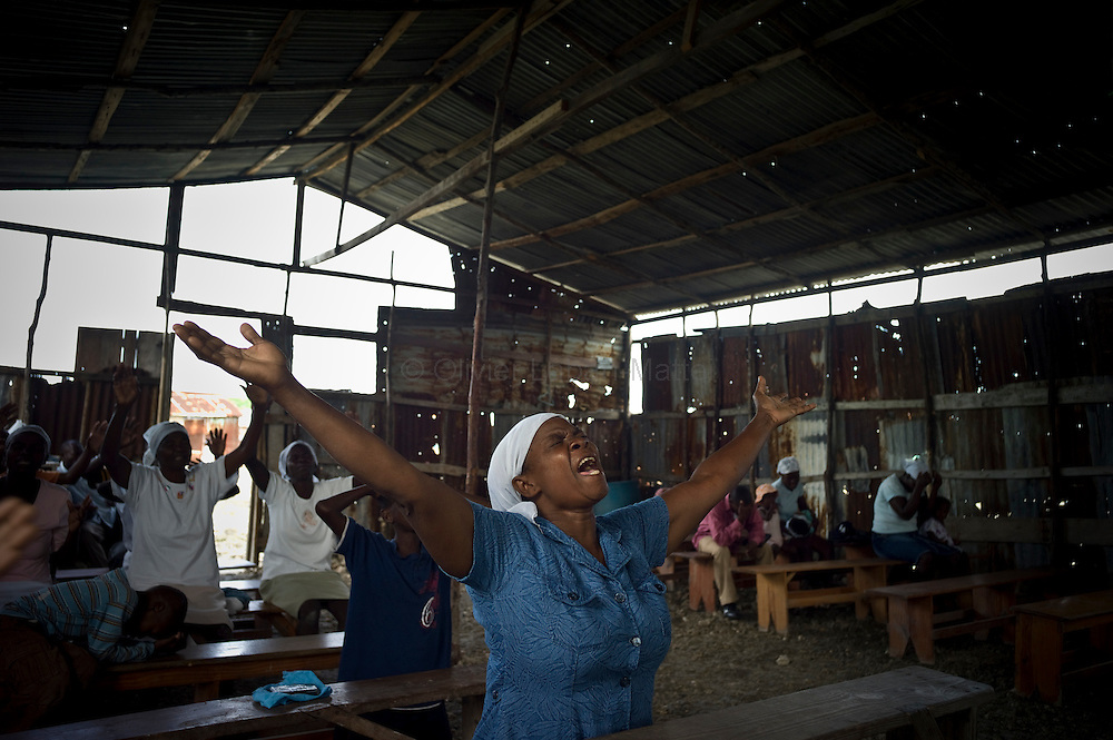 The number of cholera victims in Cité Soleil, a slum of Port-au-Prince, is increasing day by day exponentially, according to a doctor of Doctors Without Borders, esentially because of hygienic problems.///People pray in a church made with sheet metal, in the slum of Cite Soleil in Port-au-Prince.