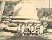 Kandy. A group of men and young monks in front of a stupa or dagoba.<br /> Natha Devale<br /> Photograph by Skeen &amp; Company.