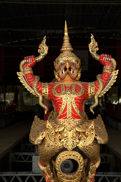 Bejeweled gold and red enamel mythical protective figure brandishing snakes  on the prow of a royal barge in the Thai Royal Barge Museum, Bangkok.  This barge is named  Narai Song Suban H.M. King Rama IX.