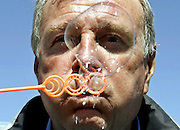 Canadian Prime Minister Paul Martin blows bubbles at a school in Regina, Saskatchewan, June 23, 2004. REUTERS/Jim Young
