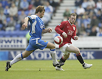 Photo: Aidan Ellis.<br /> Wigan Athletic v Manchester United. The Barclays Premiership. 14/10/2006.<br /> united's Wayne Rooney battles with Wigan's Arjun De Zeuuw