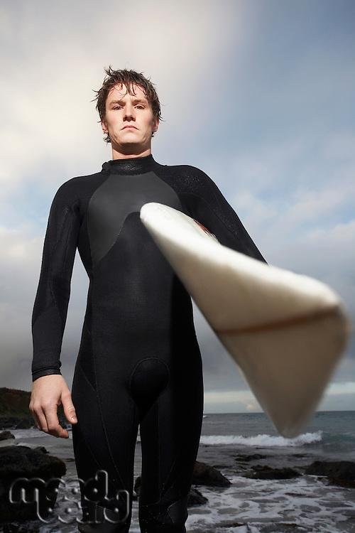 Man holding surfboard on beach portrait