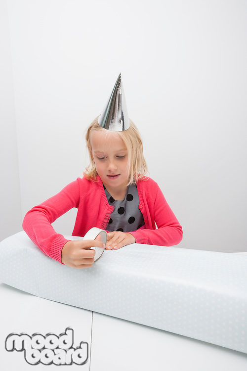 Cute girl wrapping birthday gift at table in house