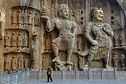The Longmen Grottoes are one of the finest examples of Chinese Buddhist art. Housing tens of thousands of statues of Buddha and his disciples, they are located 12 kilometres (7.5 mi) south of present day Luòyáng in Hénán province, Peoples Republic of China. The images, many once painted, were carved into caves excavated from the limestone cliffs of the Xiangshan and Longmenshan mountains, running east and west. The Yi River flows northward between them and the area used to be called Yique (&quot;The Gate of the Yi River&quot;). The alternative name of &quot;Dragon's Gate Grottoes&quot; derives from the resemblance of the two hills that check the flow of the Yi River to the typical &quot;Chinese gate towers&quot; that once marked the entrance to Luoyang from the south.<br /> There are as many as 100,000 statues within the 1,400 caves, ranging from an 1 inch (25 mm) to 57 feet (17 m) in height. The total.Starting with the Northern Wei Dynasty in 493 AD, patrons and donors included emperors, Wu Zetian of the Second Zhou Dynasty, members of the royal family, other rich families, generals, and religious groups.<br /> In 2000 the site was inscribed upon the UNESCO World Heritage List as &ldquo;an outstanding manifestation of human artistic creativity,&rdquo; for its perfection of an art form, and for its encapsulation of the cultural sophistication of Tang China.