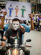 "14 JULY 2013 - BANGKOK, THAILAND:  Anti-government protesters ride a motorcycle through central Bangkok Sunday. About 150 members of the so called ""White Mask"" movement marched through the central shopping district of Bangkok Sunday to call for the resignation of Yingluck Shinawatra, the Prime Minister of Thailand. The White Mask protesters are strong supporters of the Thai monarchy. They claim that Yingluck is acting as a puppet for her brother, former Prime Minister Thaksin Shinawatra, who was deposed by a military coup in 2006 and now lives in exile in Dubai.       PHOTO BY JACK KURTZ"