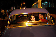 A couple in the back seat of a 1950's era American car. The embargo kept the island isolated, but failed to bring about political change.