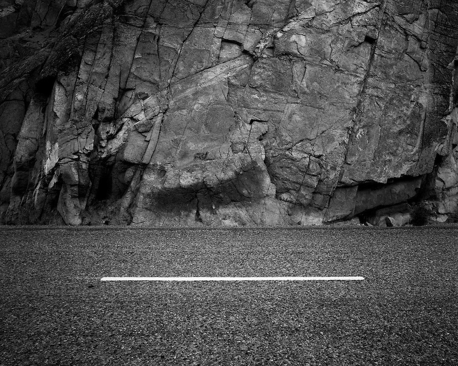 A line on the road in front of a rock outcrop