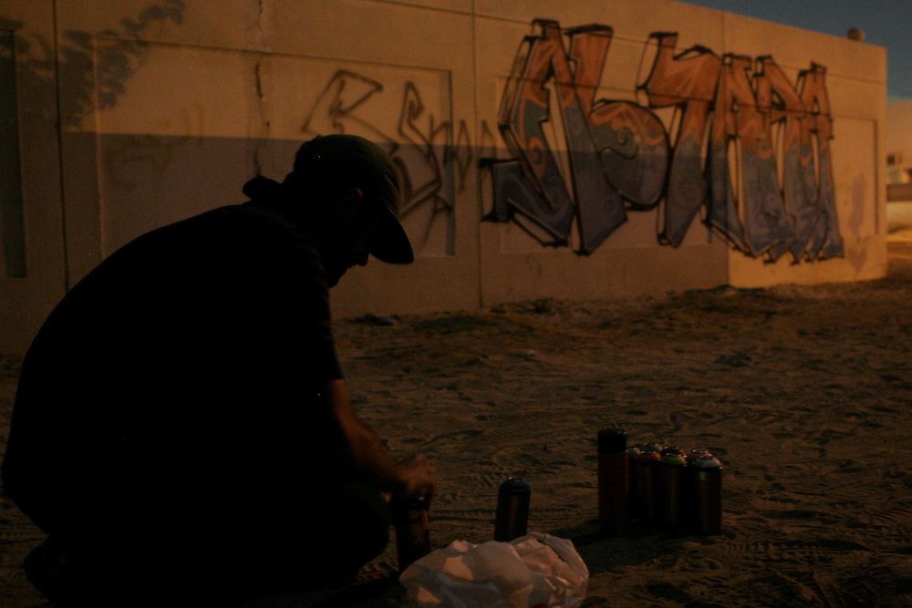 A graffiti artist getting ready to work on a wall in Dubai, where graffiti is a crime and punishable with prison time. Dubai, UAE.