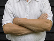 close up of an elderly man with his arms folded