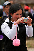 A GIRL FROM LAMUD POINTING TO HER FRIENDS WITH HER DIGITAL CAMERA.