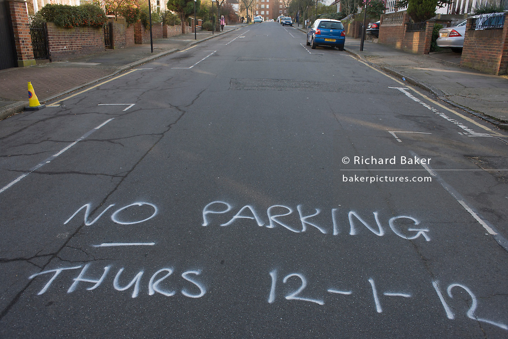 Sprayed dates for forthcoming council roadworks sprayed on a residential London street.