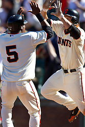 May 30, 2010; San Francisco, CA, USA;  San Francisco Giants shortstop Juan Uribe (5) is congratulated by second baseman Freddy Sanchez (right) after scoring the game winning run against the Arizona Diamondbacks during the tenth inning inning at AT&T Park.  San Francisco defeated Arizona 6-5 in 10 innings.
