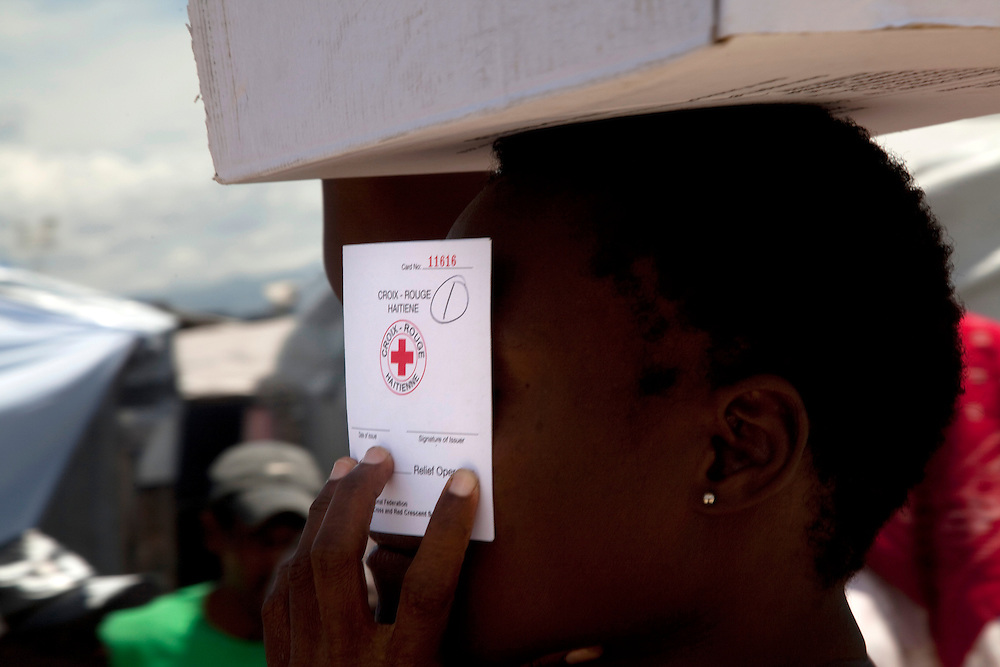 A girl holding a Haitian Red Cross card over her face in the makeshift refugee camp, La Piste, in Port-au-Prince, Haiti on July 21, 2010. La Piste (French for &quot;runway&quot;)is a settlement sprawled across the site of a disused airport and now home to an estimated 20,000 earthquake survivors living in makeshift structures.<br /> Six month after a catastrophic earthquake measuring 7.3 on the Richter scale hit Haiti on January 13, 2010, killing an estimated 230,000 people, injuring an estimated 300,000 and making homeless an estimated 1,000,000.