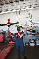 Portrait of a young female mechanic carrying oil drum on shoulder in auto repair garage
