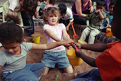 Multiracial group of nursery school children fighting over bucket in playground sandpit,