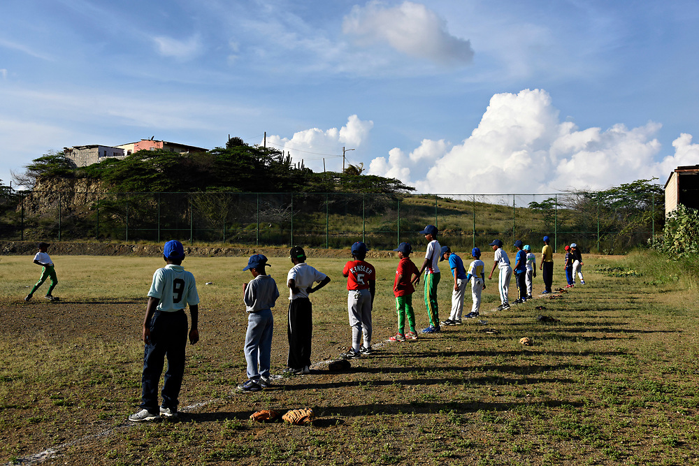 WILLEMSTAD, CURACAO - DECEMBER 11, 2014: The Marchena Hardware 7-9 year old team stretches in the outfield at Parke Shon Ki Nicasia in Willemstad before practice. (photo by Melissa Lyttle)