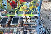 Nederland, the Netherlands, Rotterdam 23-6-2017In de overdekte markthal kun je veel verschillende culinaire producten kopen en eten. De exotische producten en retsaurants vormen een speeltuin voor de liefhebber van lekker eten. Kleurrijk interieur van de Markthal in Rotterdam, de eerste overdekte marktvloer van Nederland. De markthal is tot winnaar uitgeroepen tijdens de Dag van de Projectontwikkeling. Colorful interior of artistic market hall, winner of various international architecture awards 2015. The artwork on the ceiling, 11,000 m2, is by Arno Coenen. The building is designed by Winy Maas. The city Rotterdam was recently named by the New York Times and travel guide Rough Guide to a mustsee destination. Architect firm MVRDV FOTO: FLIP FRANSSEN