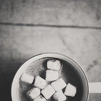 a black and white photograph of a cup of hot chocolate with little marshmallows in it.