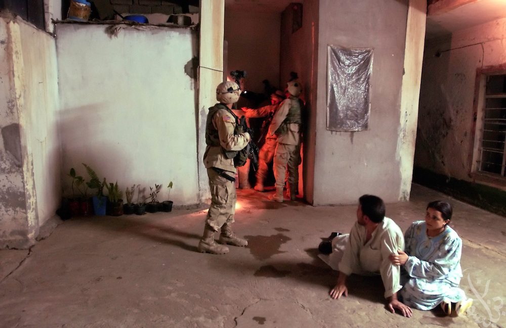 An Iraqi couple cower as U.S. Army 101st Airborne 3rd Battallion 502nd Infantry soldiers search their home during a night time raid July 29, 2003 in the Northern Iraqi city of Mosul.