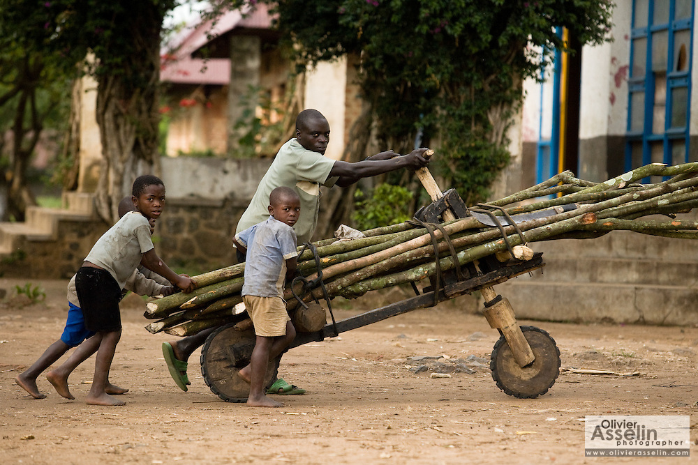 Three boys help a man push a wooden scooter (chikudu) loaded with logs in Rutshuru, 70km north of Goma, Eastern Democratic Republic of Congo, on Thursday December 11, 2008..
