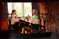 Fireplace at the Felin Fach Griffin<br /> Couple dining next to window in background<br /> Powys<br /> South<br /> Pubs and Restaurants