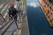 Passerby comes down the stairway of pedestrian bridge across Naviglio Grande (canal) near to via Casale at Ticinese district in Milan, January 20, 2011. Reflections of houses in the water. © Carlo Cerchioli..Passante scende le scala del ponte pedonale sul Naviglio Grande vicino a via Casale al quartiere Ticinese a Milano, 20 gennaio, 2011. Nell'acqua riflessi delle case.