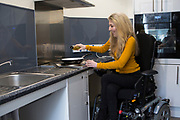 Sophie cooking on a lowered hob in the shared kitchen at University of Bath.
