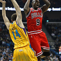 February 12, 2011; New Orleans, LA, USA; Chicago Bulls small forward Luol Deng (9) shoots over New Orleans Hornets power forward Jason Smith (14) during the first quarter at the New Orleans Arena.   Mandatory Credit: Derick E. Hingle