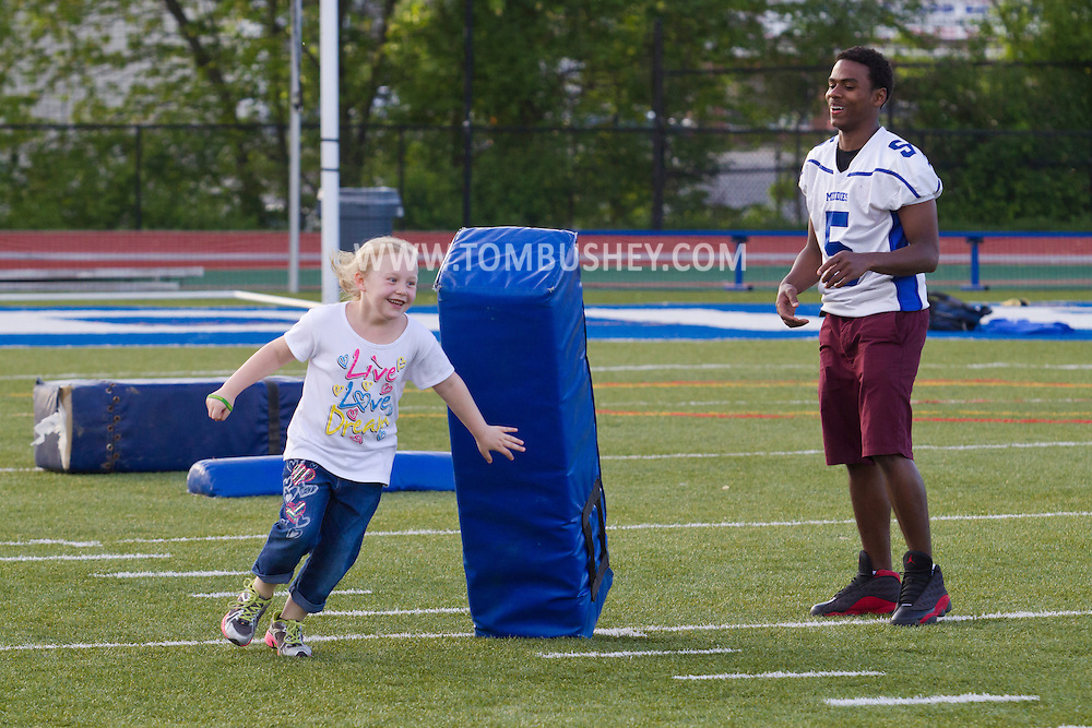 Middletown, New York - A young girl runs around a cushion held by a Middletown High School varsity football player at Faller Stadium during Family Fun Night on May 17, 2013.
