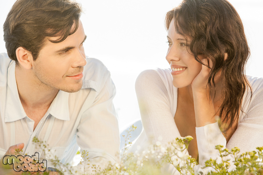 Loving couple looking at each other while lying against clear sky