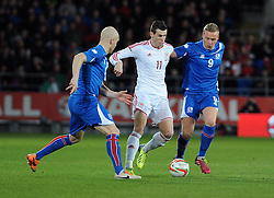 Gareth Bale of Wales (Real Madrid) is chased down by Kolbeinn Sigthorsson (Ajax) of Iceland and Emil Hallfredsson (Hallas Verona) of Iceland - Photo mandatory by-line: Dougie Allward/JMP - Tel: Mobile: 07966 386802 03/03/2014 -
