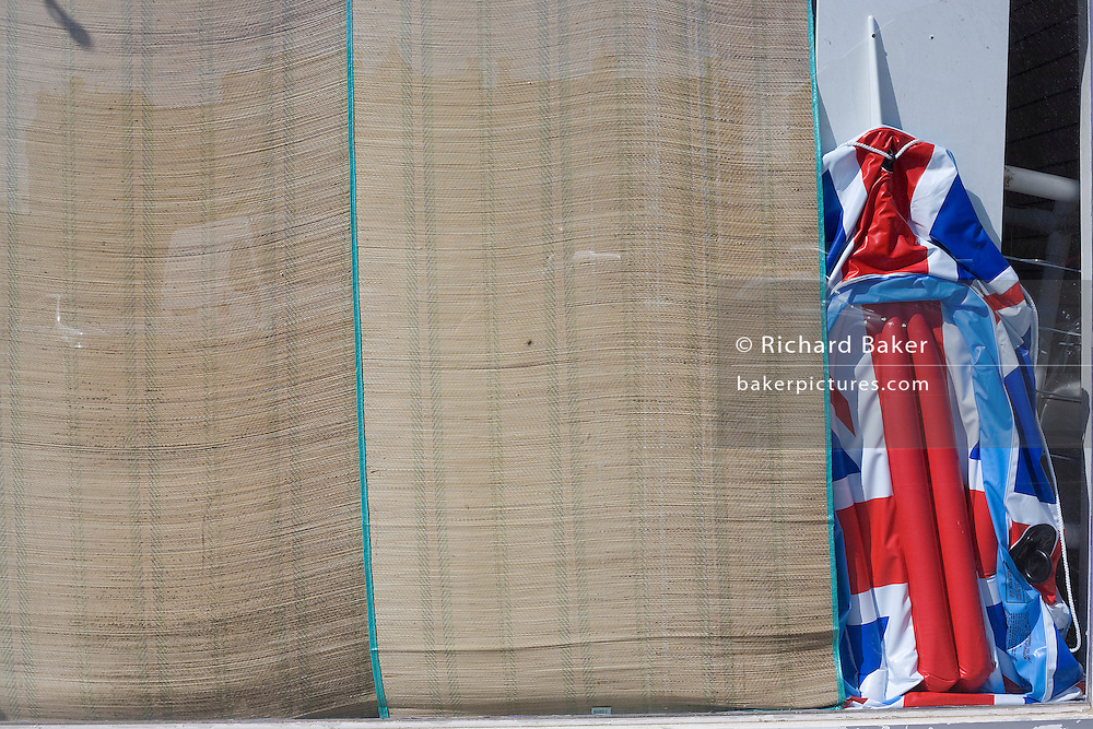 A deflated union jack flag beach lilo is abandoned in in a window of a seaside shop called The Tropicana in Weston-super-Mare, a victim of the UK recession and the tourist trade.