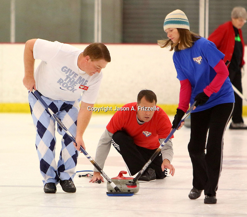 Tony Jacobs, center watches Patrick Rameas, left and Maggie Schaber sweep after he delivers the stone during a curling match at the Wilmington Ice House. (Jason A. Frizzelle)