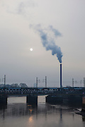 Hamburg on a winter morning, stean comes from a smokestack, as the sun comes through a the fog.