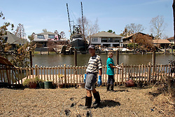 08 Sept 2005.  New Orleans, Louisiana. Hurricane Katrina aftermath. <br /> Venetian Isles in East New Orleans, where the tidal surge washed over the land and devastated homes and property. John and Peggy Lala survey the damage of their mud filled flood ravaged home with the new addition of a shrimp boat across the canal.<br /> Photo; ©Charlie Varley/varleypix.com