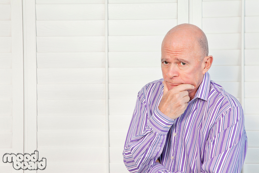 Senior man in pensive mood with hand on chin