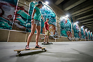 Longboarding past a large mural in downtown Grand Rapids.