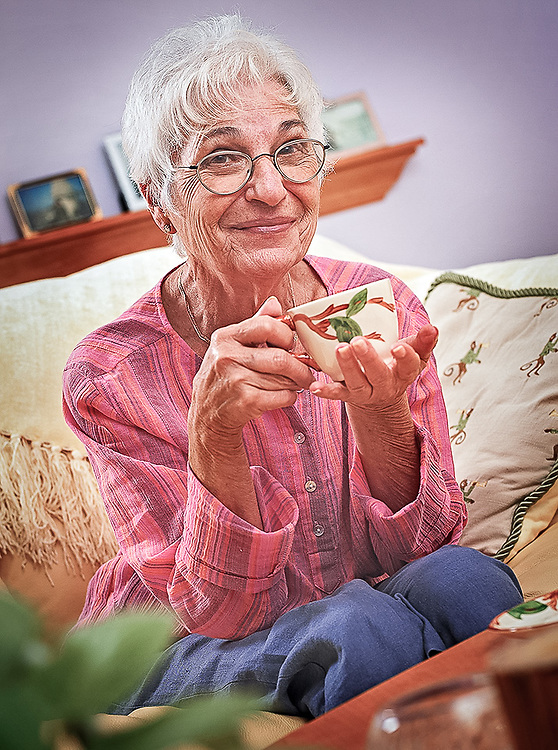 Mature woman with tea cup seated on couch