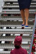 Cabin crew hostess at the bottom of steps a Qatar Airways Boeing 787 at the Farnborough Air Show, UK.